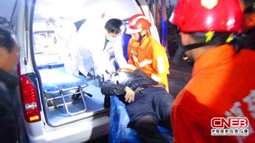 消防人员将被困司机抬上救护车。