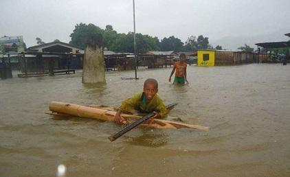 """今年三月份, 热带气旋""""爱娜沃""""(Enawo)期间,儿童在马达加斯加被淹没的街道上穿行(图为:联合国儿童基金会马达加斯加)"""