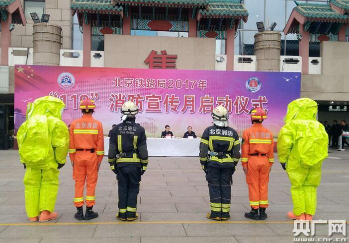 """""""119""""消防宣传月启动仪式现场,消防员为市民展示消防战斗服。"""