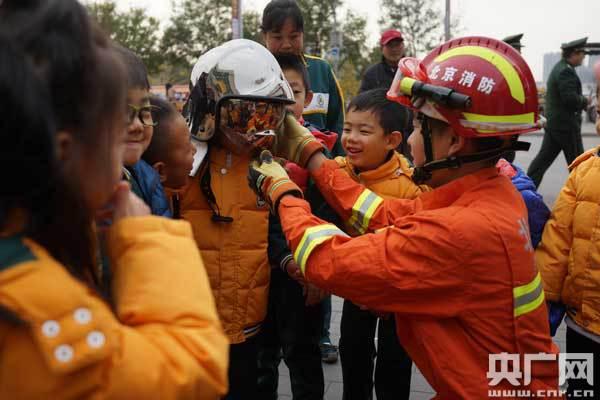 消防员为幼儿园小朋友们讲解消防器材的使用/张佳琪 摄