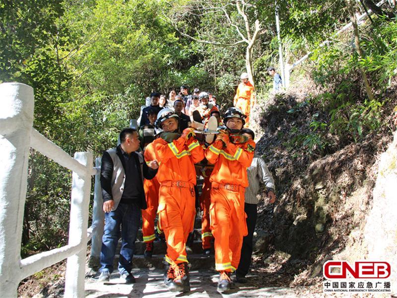 消防官兵用担架将伤者抬下山