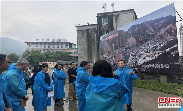 參演人員在北川地震遺址萬人紀念碑前聆聽曾經參與報道的同事講述