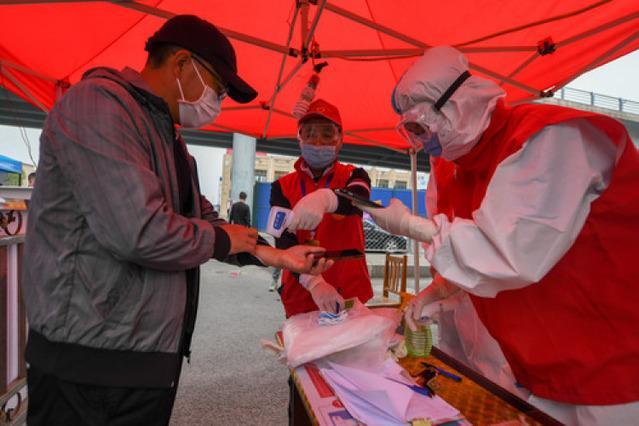 志愿者正在为小区门口出入人员测量体温,右三为杨媛