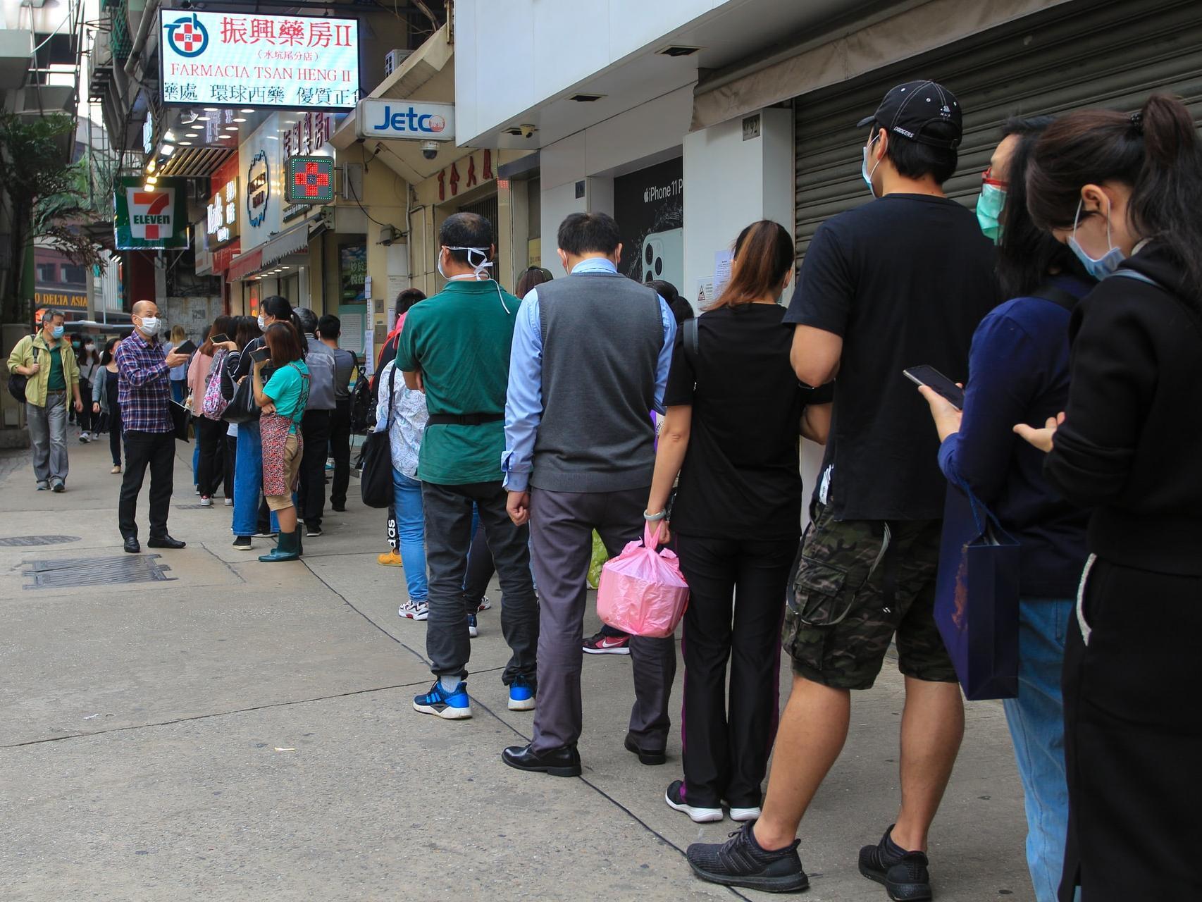 在澳门,市民在一家药房前面排队购买口罩。为避免囤积、库存不足和价格上涨,政府制定了一项计划,为所有市民提供口罩